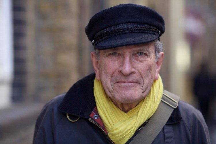 Street photography portrait of a man in a dark peaked capped and yellow scarf, looking at the camera