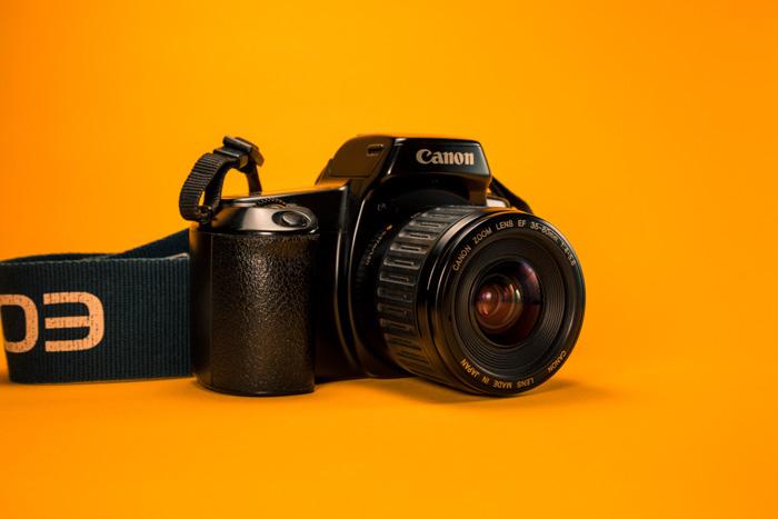 a canon DSLR camera on a bright orange surface