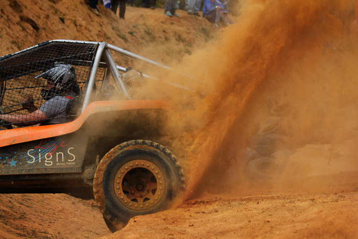 A photo of a race care driving through sand emitting dust clouds behind him