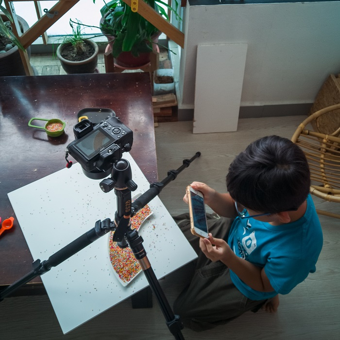 a man using white card under a camera for photography at home