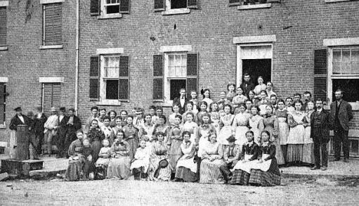 """Group, presumably boarders, in front of boardinghouse"". (Source: University of Massachusetts)."