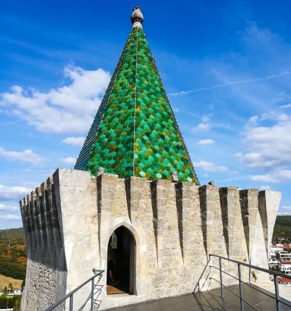 Coruchéu piramidal numa das torres do Castelo de Porto de Mós, com telhas de escama verdes, representando a Casa de Ourém
