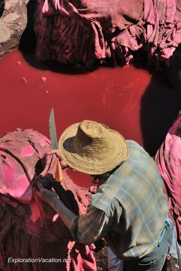 Vat of red dye with leather and worker