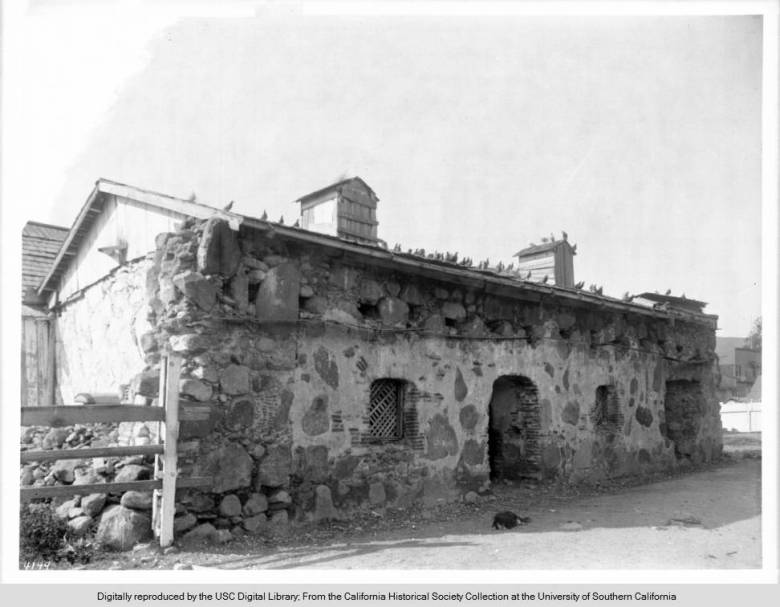 A_dog_sleeps_on_the_ground_in_front_of_the_Priests_residence_of_Mission_San_Luis_Obispo_de_Tolosa_ca1900