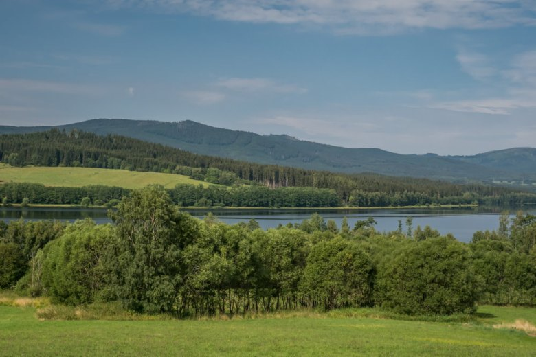 meadows, forests, and mountains along Lake Lipno