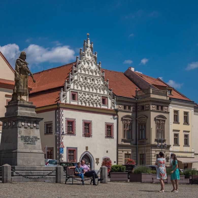 Statue and elaborately decorated buildings where people sit along the square