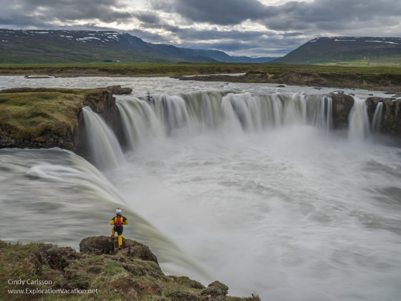 man standing at the edge of a massive waterfall