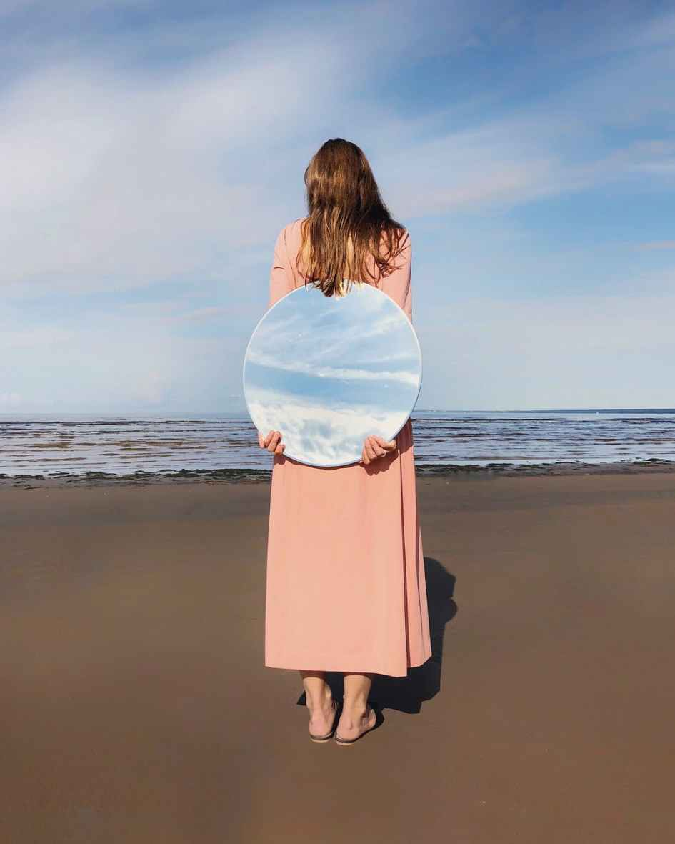 woman standing beside shore holding mirror on her back