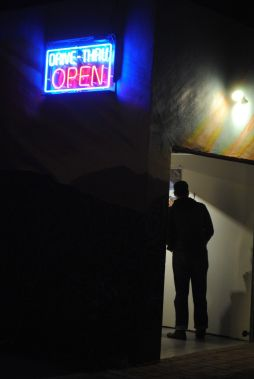 """Scene from the Drive-Thru Gallery, showing illustrations by various artists making """"Manifestos."""""""