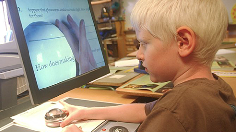 Elementary child using magnifier and computer enlargement
