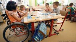 Child in wheelchair at low table