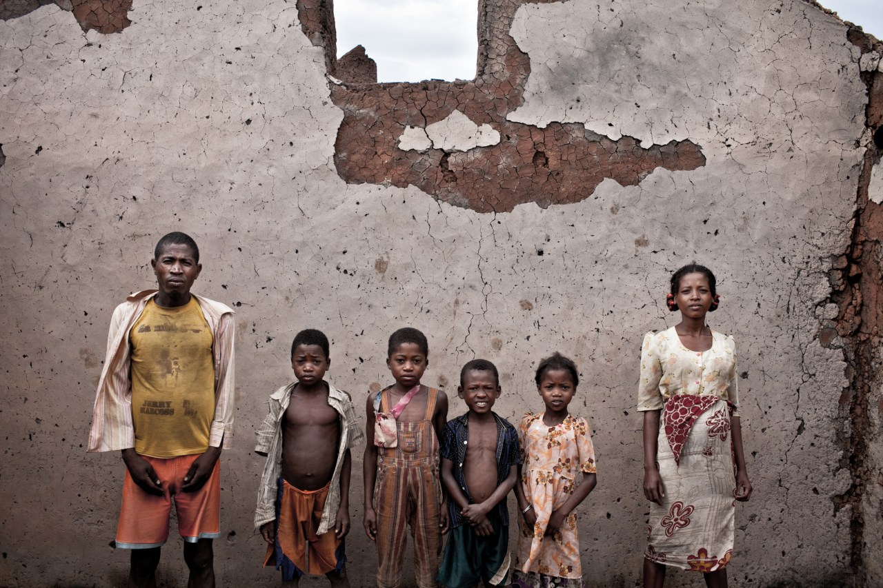 """Jean-Baptiste poses with his wife and kids in their house's ruins. """"We were coming back from the rice fields when we saw the military men burning our house down. I remember it well, it was a Monday around noon. They took one of our zebus for them to eat."""""""