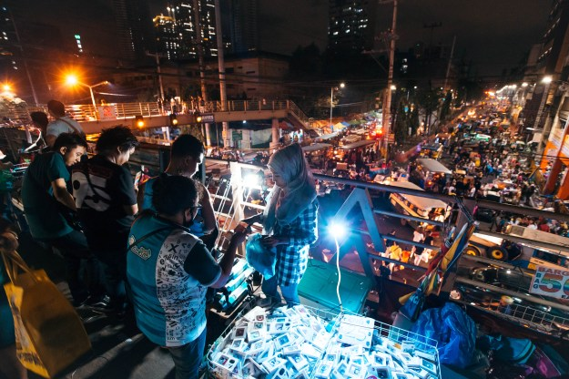 """1. A man poses in front of a """"Belen,"""" a creche representing the Nativity scene, in the streets of Manila. / 2. Millions of people visit the Recto-Divisoria night markets during the holiday season."""