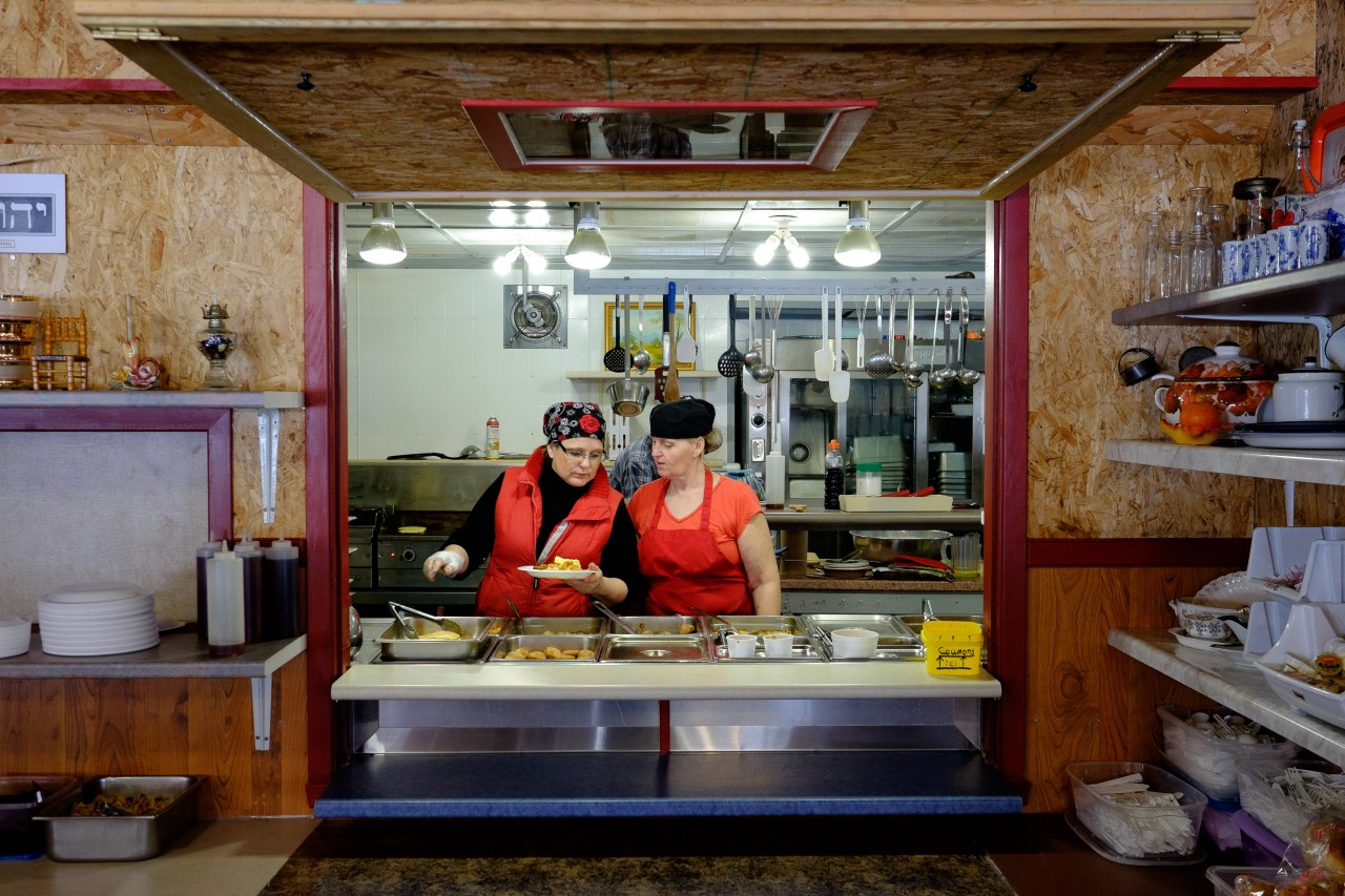Simone Vezina (left) serves food in her sugar shack in Saint-Modeste, Québec . Popular items are pancakes, sausages, and maple syrup.