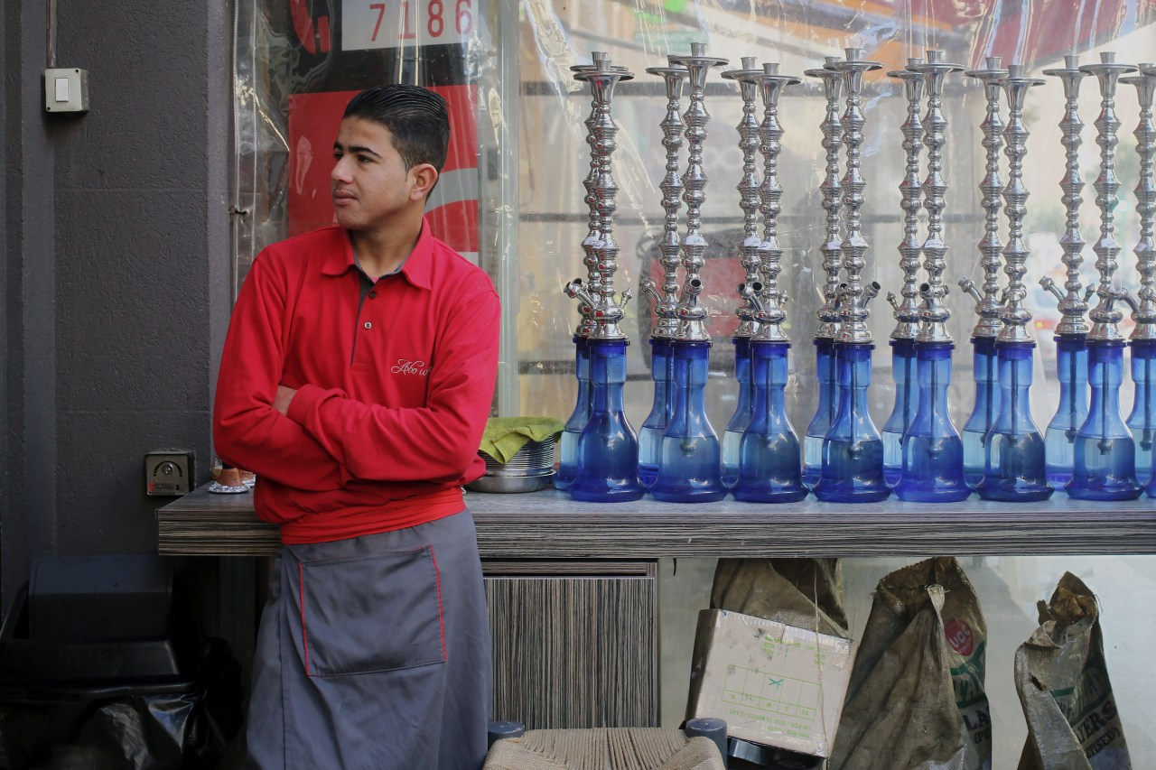 A Syrian employee of the restaurant stands next to hookah pipes.