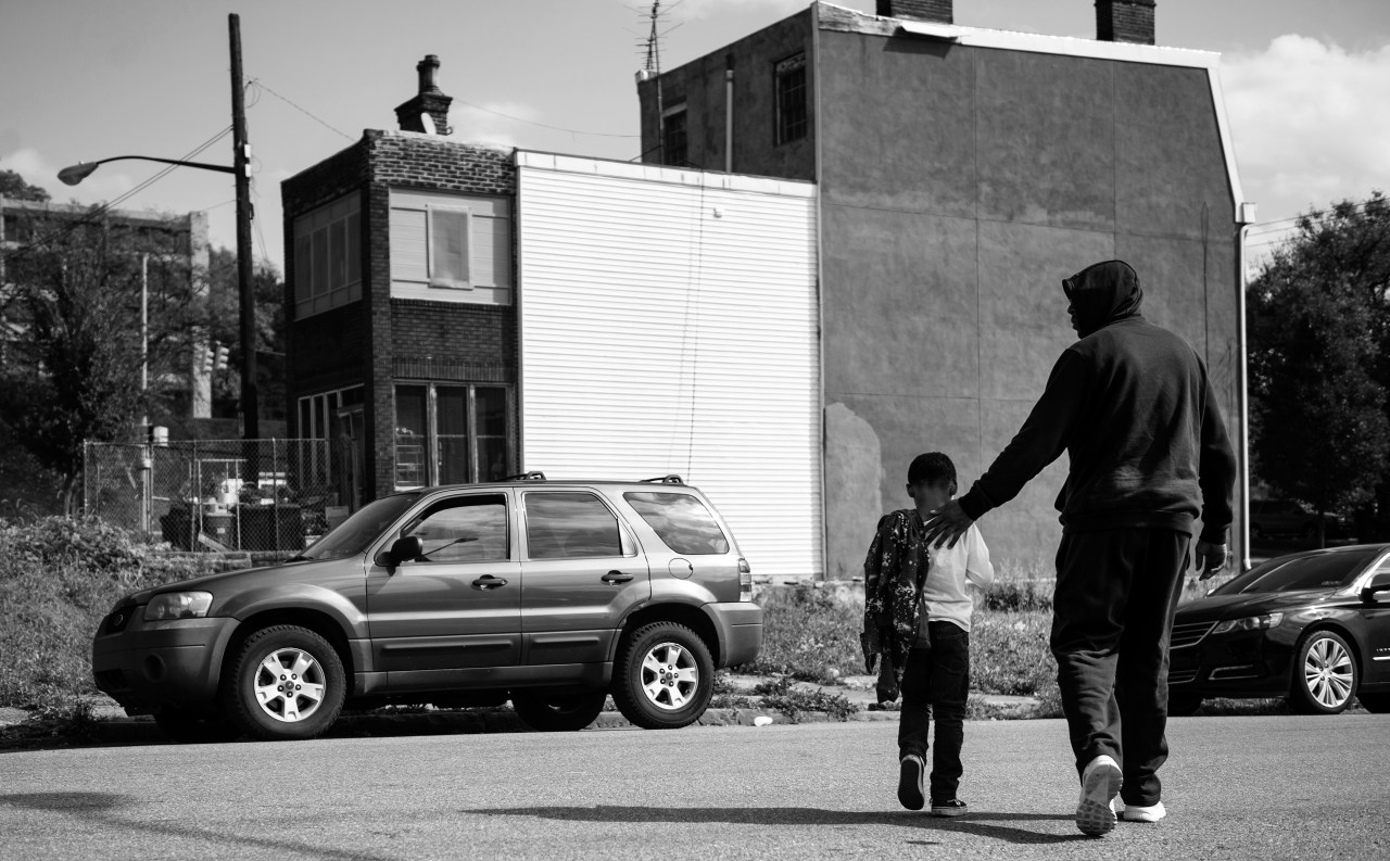 Chris Collins, walks his son Chris across the street after receiving his weekly haircut at Dave's Barber Shop. Between work and home life, the two share this trip as a special father and son moment.