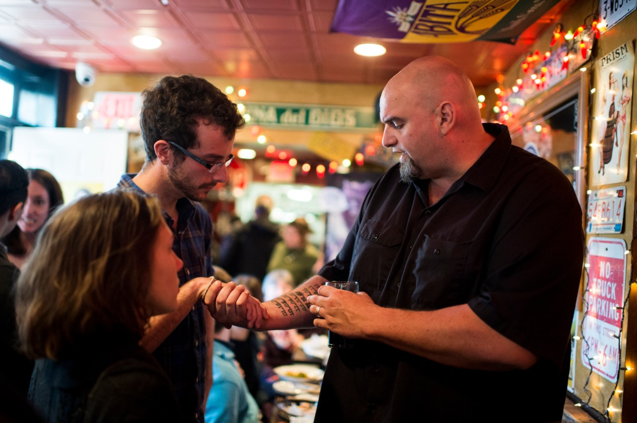 John Fetterman shows off his tattoos as he speaks with supporters during his meet and greet campaign stop at the Interstate Drafthouse in Philadelphia on Sunday, April 3, 2016. (Photo By Bill Clark/CQ Roll Call via Getty Images)