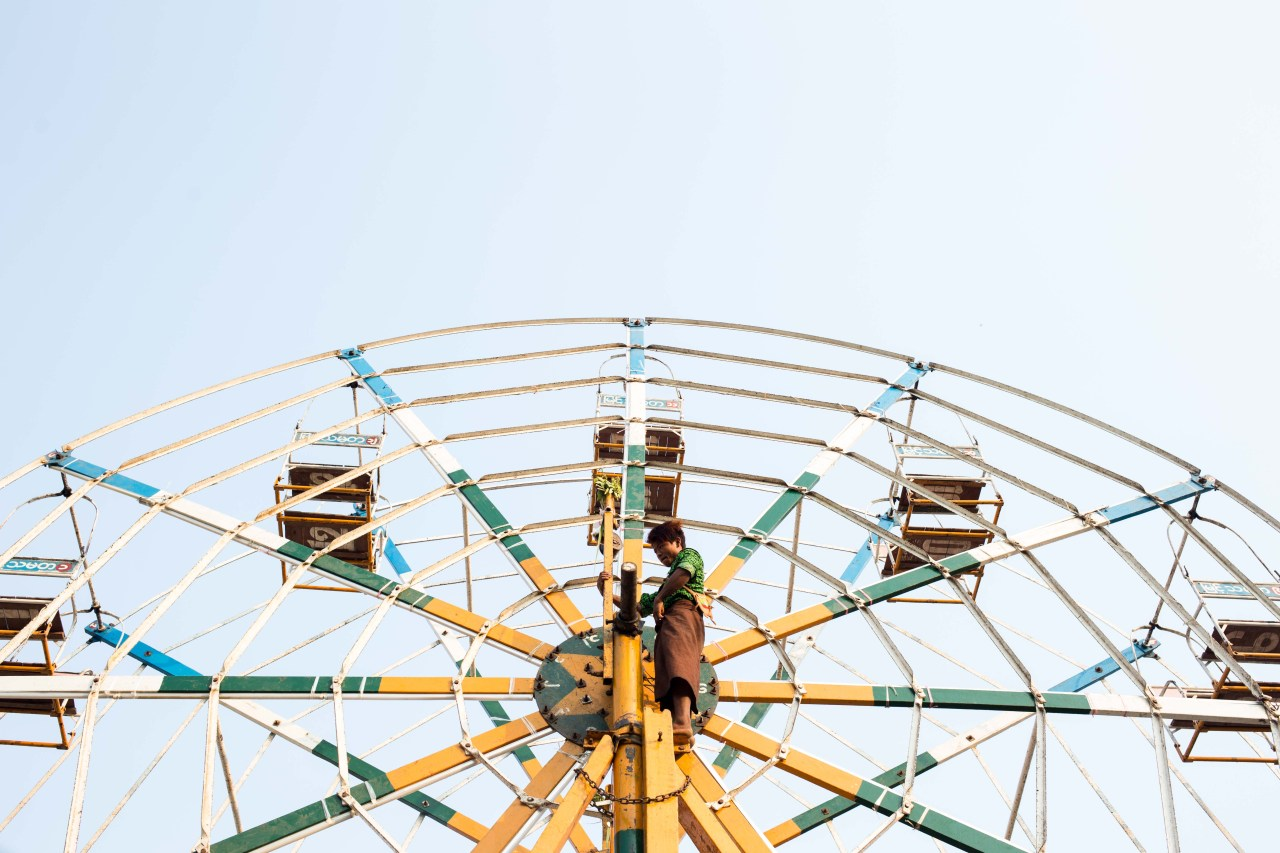 A Ferris wheel operator at Shwe San Daw Pagoda festival in the Twantay township, on the outskirts of Yangon.