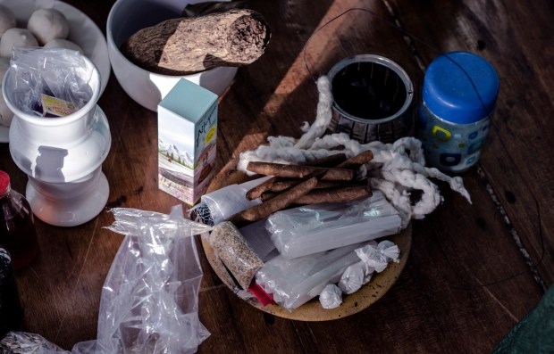From cigars and obscure plant roots to thin, white candles, Mãe Marta meticulously prepares the materials she will need to perform the spiritual cleansing of the house.