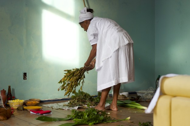"""Photo 1: Plants with names such as """"path opener,"""" """"battle winner"""" and """"knock it all down"""" are sprinkled with pemba, roots and herbs that are  finely ground and correspond to the Orisha for which they are destined. Photo 2: Mãe Marta gathers plants to cleanse the physical, and spiritual energy of the house and its residents."""