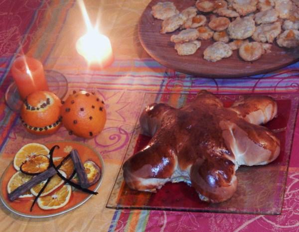Notre table de solstice d'hiver : des biscuits ronds à l'orange, une brioche en soleil, des bougies, des oranges décorées avec des clous de girofle