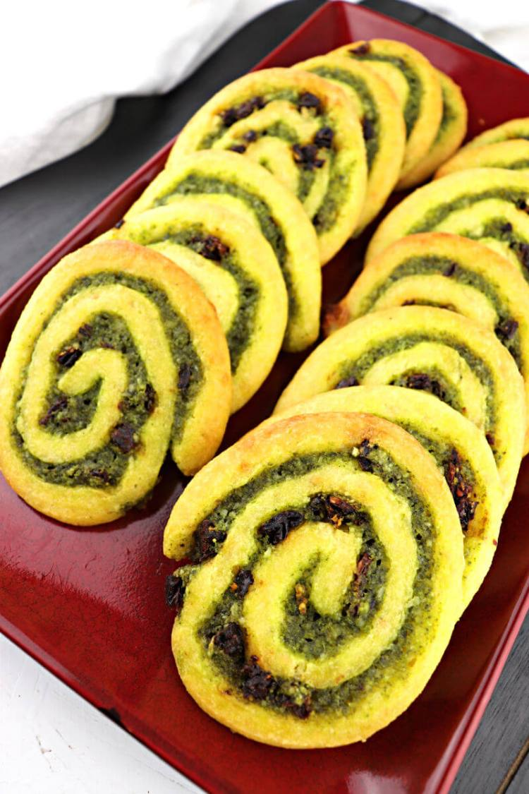 Flavorful parmesan, basil, garlic, and sun-dried tomatoes flavor these keto pesto pinwheels. Perfect for a low carb appetizer or gluten-free game day snack. #ketoappetizer #ketorecipes