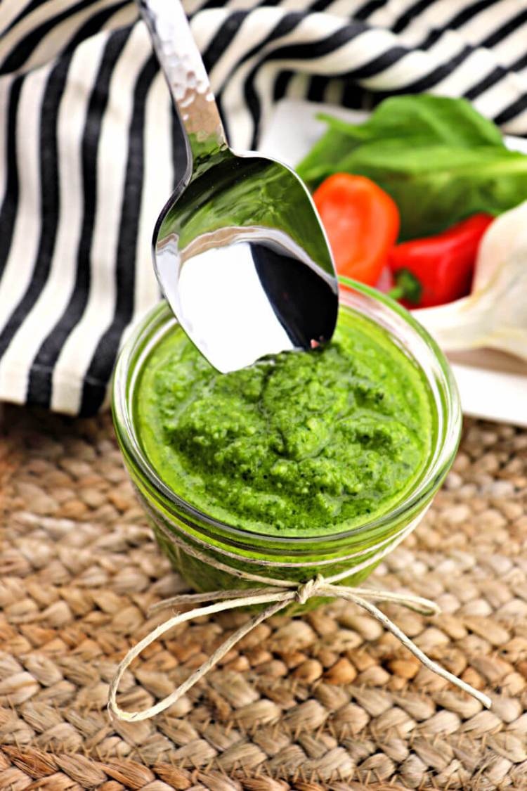 Spoon dips into a jar of basil keto pesto sauce. #ketorecipes #italianketo