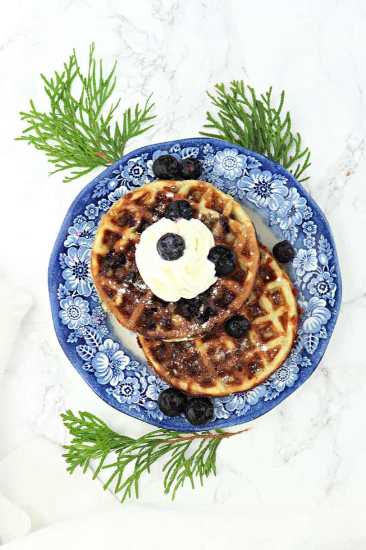 Keto Blueberry Chaffles are filled with traditional morning flavors! Low carb, super-easy to make and delicious, you won't believe they're sugar-free and gluten-free. #chaffles #blueberrychaffles #ketobreakfast