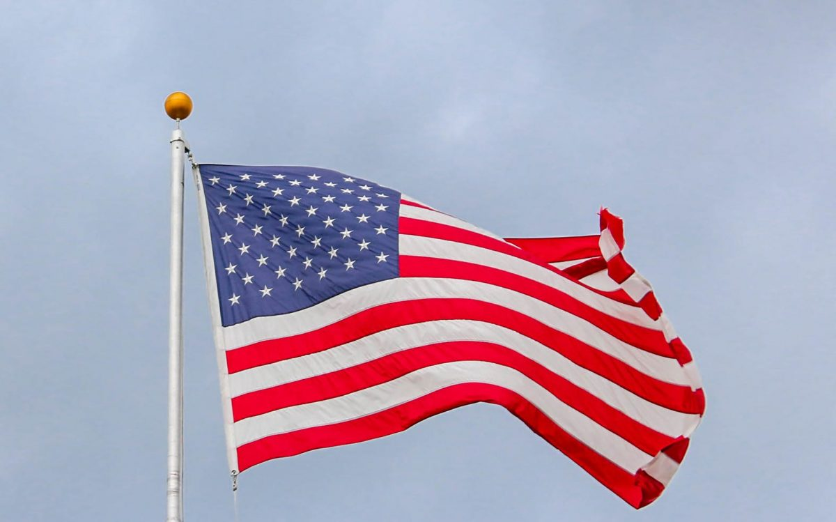 USA flag waving on a white metal pole