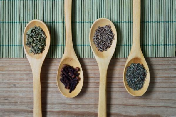 Herbs resting on wooden spoons