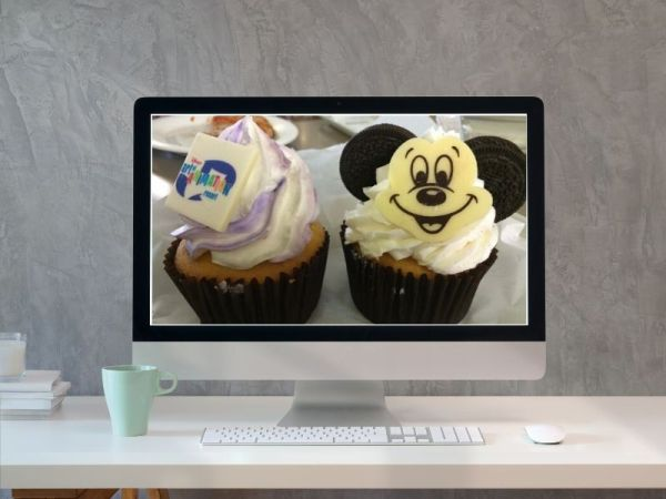 Computer with Disney-themed cupcakes on the monitor