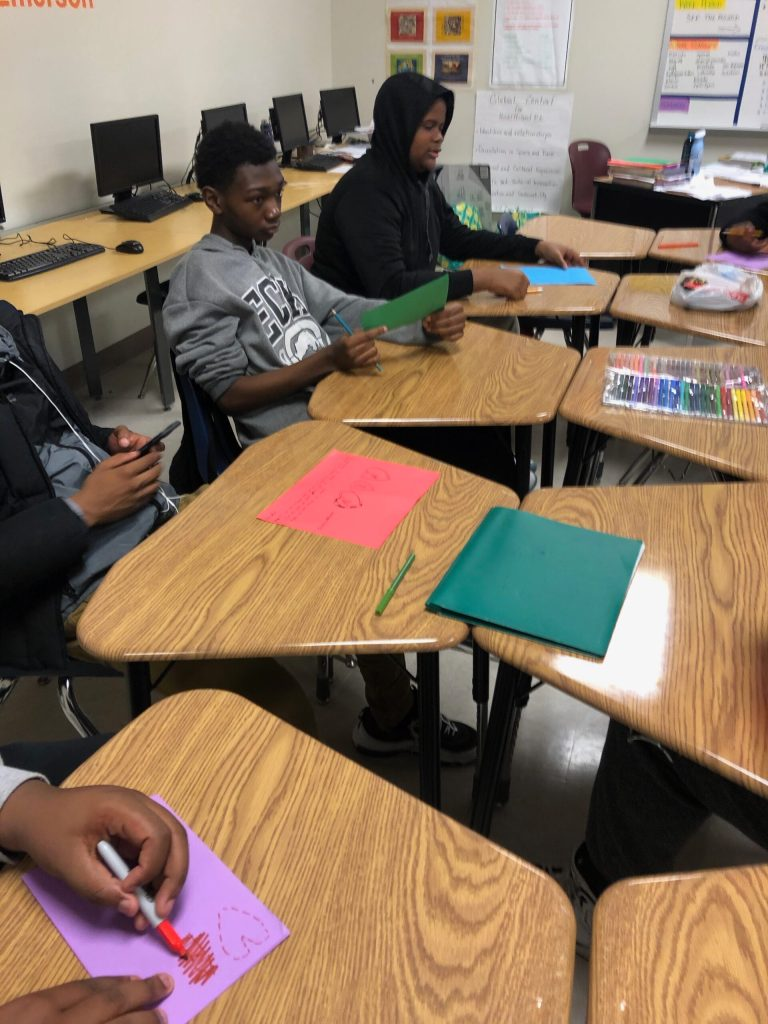 Image of two young, African American males sitting as desks writing on brightly color paper. You can see other desks with the paper on it but can only see parts of the students sitting at those desks.