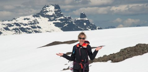 a woman stands on the ridge below Mount Heber with Warden and Victoria Peaks in the background