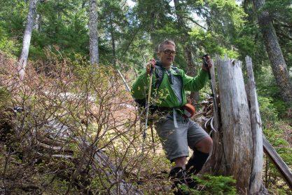 a man walks down a logging slope