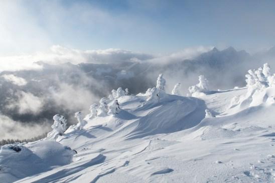 on the summit of Mount Elliot, cloud draped Mount Ashwood and Bonanza Peak in the background