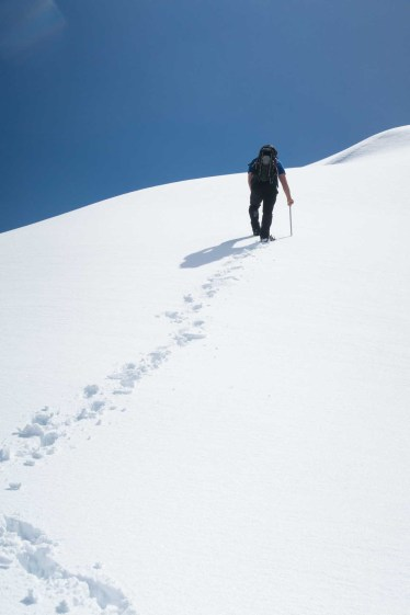 a man walking up a steep snow slope to Canoe Peak