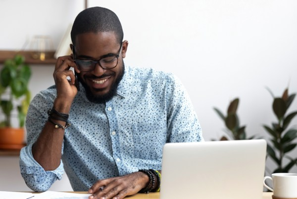 Image: Handsome african manager sitting at office desk in front of laptop hold mobile phone make pleasant business or informal call.