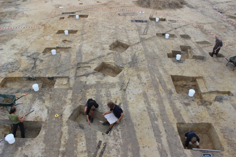In de middeleeuwen woonden de inwoners van Maalte in woonstalhuizen. Vandaag blijven enkel de paalsporen over, aangeduid met witte emmers. De archeologen doen dienst als schaallat: middeleeuwse huizen, waar woon- en stalgedeelte onder één dak lagen, waren reusachtig © De Logi & Hoorne