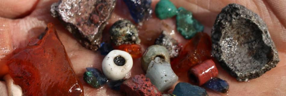 Een handvol vondsten uit de zeef, aardewerk, barnsteen en vooral veel kralen © Northern Emporium