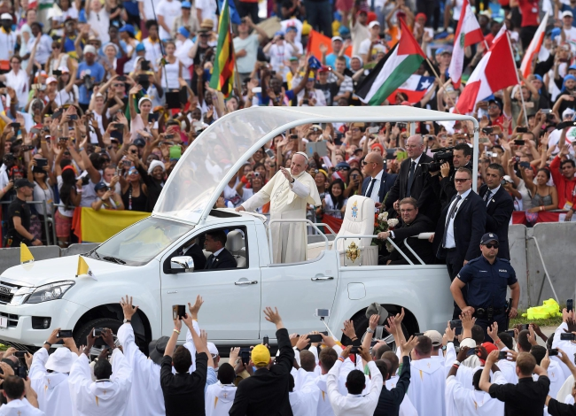 Pope Francis waves from the Popemobile upon his arrival to celebrate a Mass for the World Youth Day at the Campus Misericordiae in Brzegi, Poland, 31 July 2016. Photo: EPA/DANIEL DAL ZENNARO