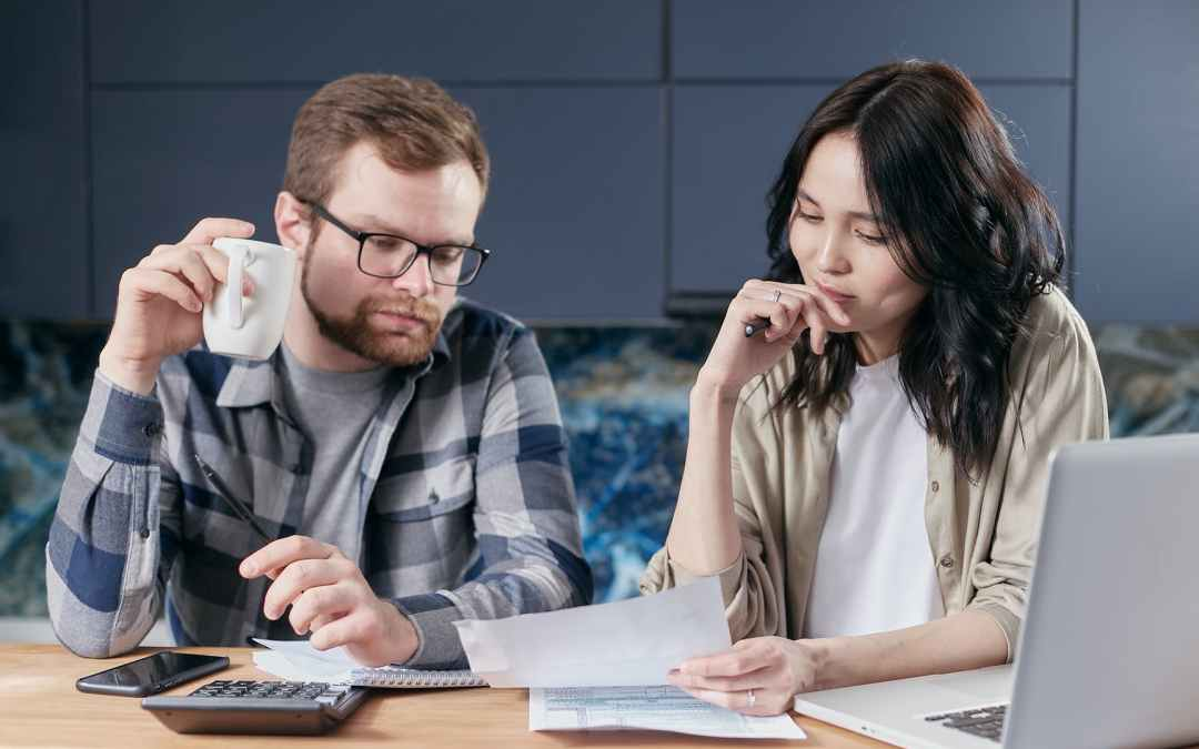 coworkers at table with documents and calculator near laptop
