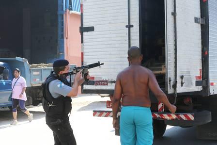 Um PM aponta uma arma para a carroceria de um caminhão