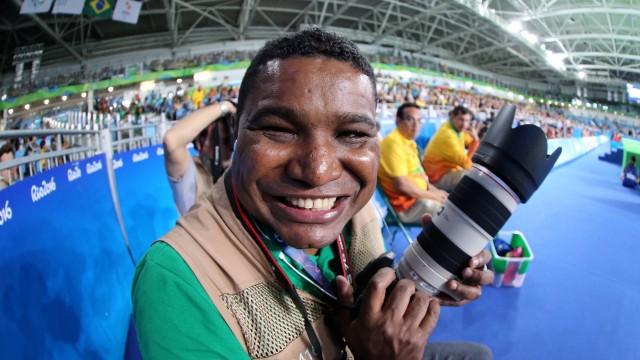 Foto de João Maia sorrindo com uma câmera profissional de blusa verde e colete dentro de um estádio dos jogos paralímpicos 2016