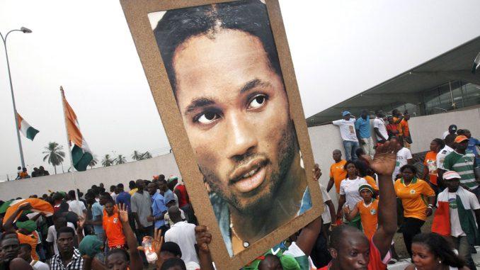 Torcedores seguram a foto de Didier Drogba, o maior ídolo da Costa do Marfim.