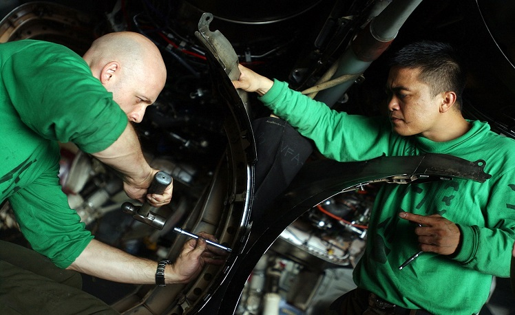 """060617-N-5549O-045 Philippine Sea (June 17, 2006) - Aviation Structural Mechanic 2nd Class Chris Luebcke, left, and Aviation Structural Mechanic 3rd Class Rowel Dela Cruz replace turkey feathers from exhaust fairings on an F/A-18C Hornet assigned to the """"Stingers"""" of Strike Fighter Squadron One One Three (VFA-113) aboard the Nimitz-class aircraft carrier USS Ronald Reagan (CVN 76). Ronald Reagan and embarked Carrier Air Wing One Four (CVW-14) are currently on a regularly scheduled deployment in support of the global war on terrorism and maritime security operations (MSO) and participating in Exercise Valiant Shield 2006. Valiant Shield focuses on integrated joint training among U.S. military forces, enabling real-world proficiency in sustaining joint forces and in detecting, locating, tracking and engaging units at sea, in the air, on land and cyberspace in response to a range of mission areas. U.S. Navy photo by Photographer's Mate 3rd Class Kevin S. O'Brien (RELEASED)"""