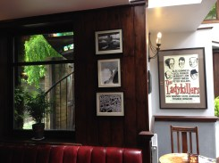 Movie photos mounted on the wall featuring stars who came to the pub.