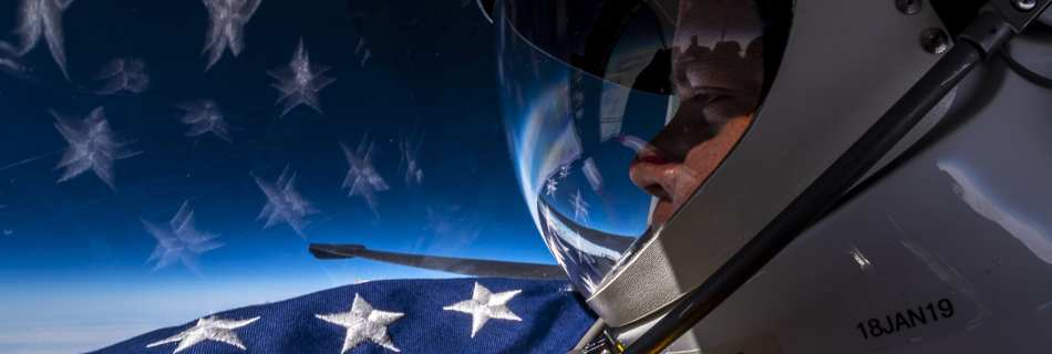 Extreme Ross stares over the stars from a flag out past the wing of a U-2