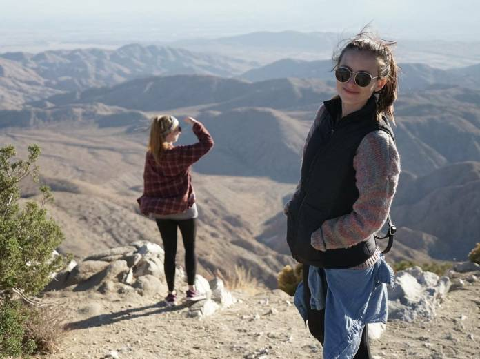 The author, Tanza Loudenback, stands on top of a mountain, smiling at the camera while wearing sunglasses, a thick sweater, and a down vest.
