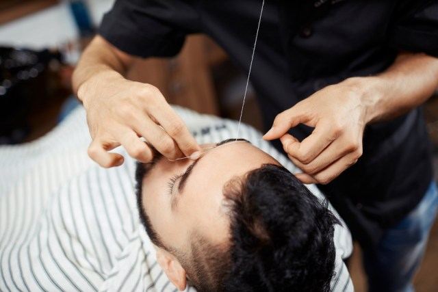 A male client getting his brow hairs removed