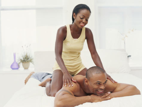 Young couple in bedroom, woman massaging man, smiling